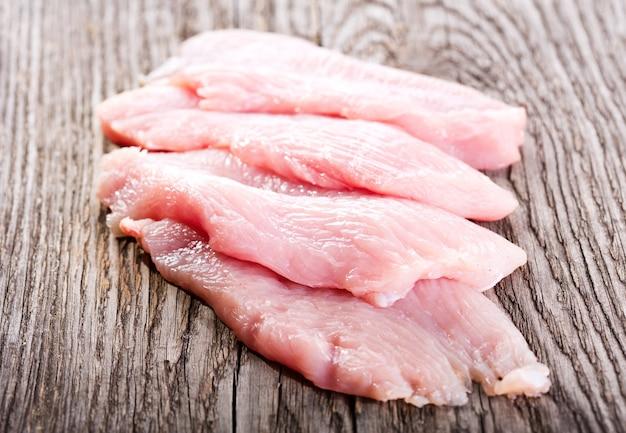 Peitos de frango crus na mesa de madeira