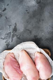 Peitos de frango em fundo cinza, vista superior com espaço de cópia