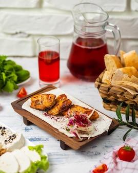 Peitos de frango grelhados marinados saudáveis cozidos em um churrasco de verão e servido em lavash com ervas frescas, vinho, pão em uma placa de madeira, close-up vista