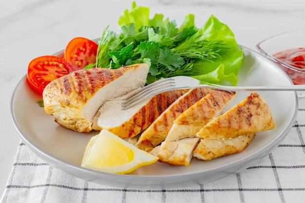 Peitos de frango grelhados servidos em um prato com salada e legumes. alimentos dietéticos.