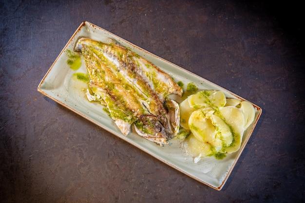 Peixe ao molho verde com batatas em um fundo preto, em um prato branco