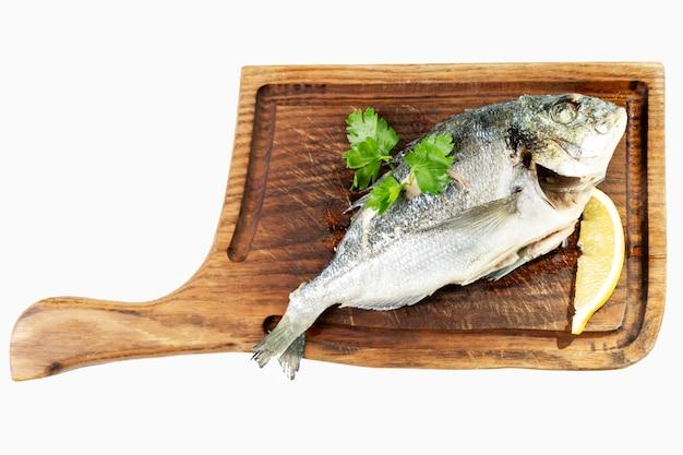 Peixe apetitoso com limão servido em uma placa de madeira.