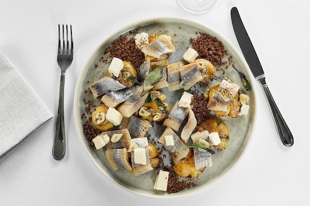 Peixe arenque com fatias de batata e cebola roxa, pão de centeio na mesa branca. vista do topo.