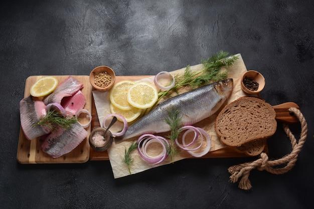 Peixe arenque na placa de madeira com ervas pimenta, cebola roxa e limão em fundo preto