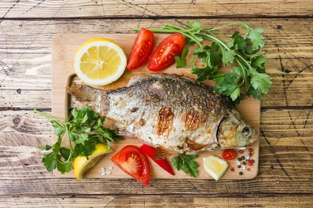 Peixe assado carpa com legumes e especiarias em uma mesa de madeira.