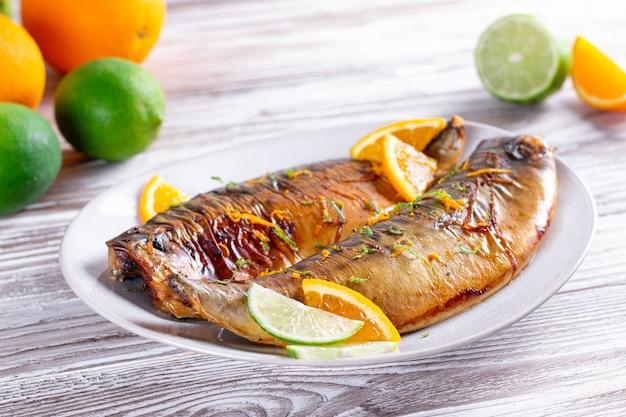 Peixe assado delicioso com fatias de limão e laranja, especiarias em um prato, close-up. delicioso prato de frutos do mar
