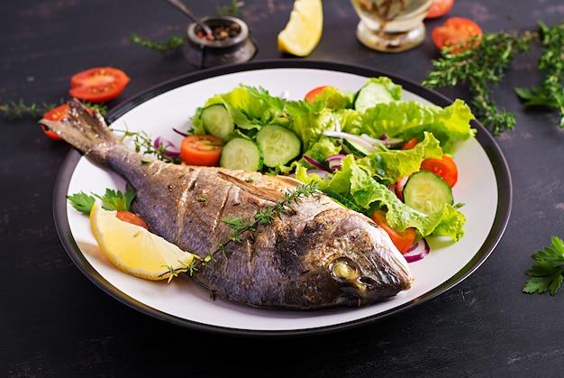 Peixe assado dorado com limão e salada fresca em chapa branca sobre fundo rústico escuro. jantar saudável com o conceito de peixe. dieta e alimentação limpa