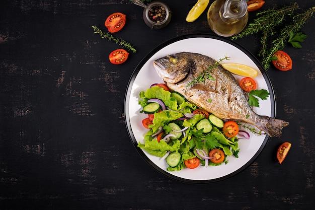 Peixe assado dorado com limão e salada fresca em chapa branca sobre fundo rústico escuro. vista do topo. jantar saudável com o conceito de peixe. dieta e alimentação limpa