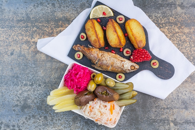 Peixe assado e batata em uma tábua ao lado de uma tigela de legumes em conserva.