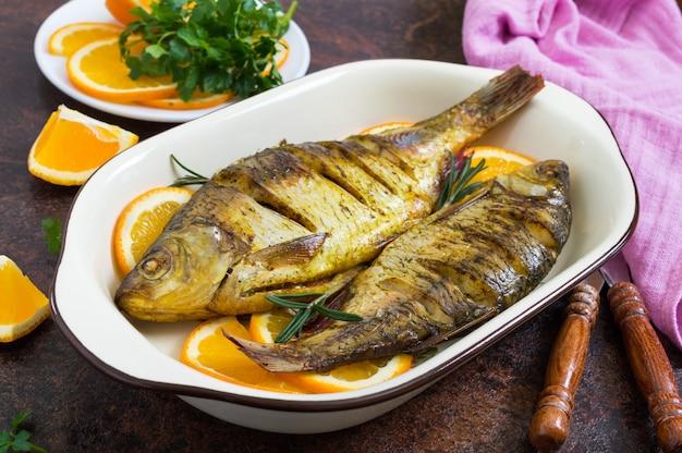 Peixe barata assado com legumes e laranjas em uma tigela de cerâmica. menu de dieta.
