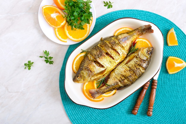 Peixe barata assado com legumes e laranjas em uma tigela de cerâmica. vista do topo. menu de dieta.