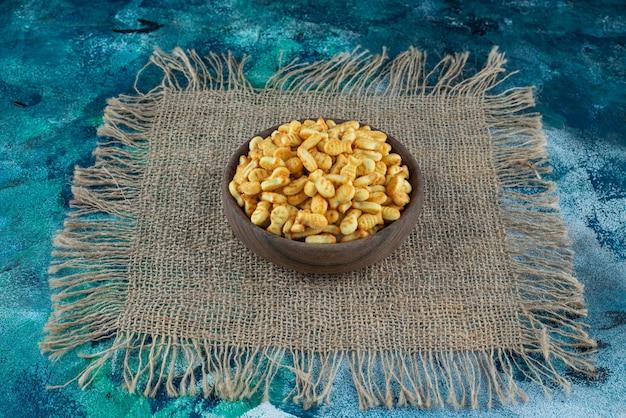 Peixe biscoito em uma tigela sobre uma textura, na mesa de mármore.