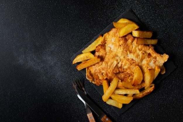 Peixe britânico tradicional com batatas fritas. em uma placa preta e um fundo preto. espaço para texto. vista superior, plana leigos.