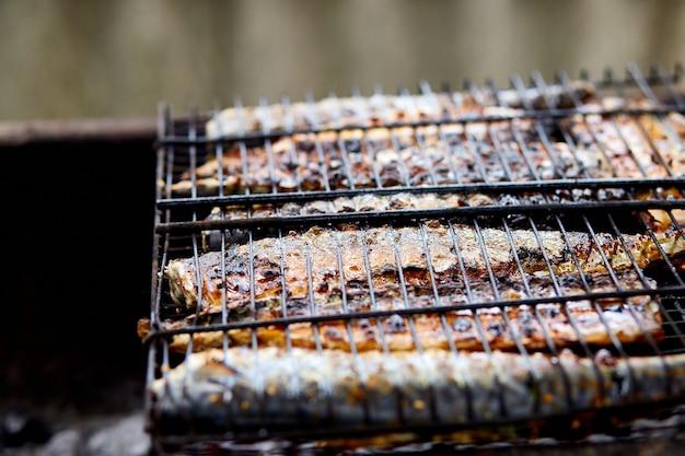 Peixe carapau grelhado, cozido na grelha ao ar livre, flui comida saborosa e fresca, piquenique ao ar livre, recreação.