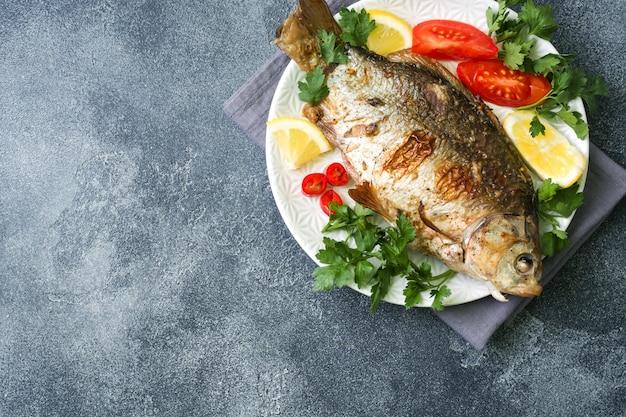 Peixe carpa assada com legumes e especiarias em um prato sobre uma mesa escura