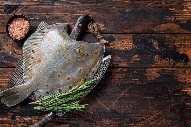 Peixe chato de solha crua a bordo de açougueiro com faca. fundo de madeira escuro. vista do topo. copie o espaço.