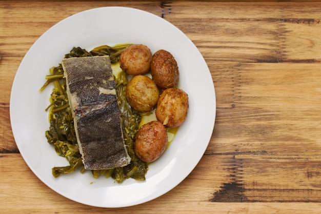 Peixe com batata e legumes no prato branco e copo de água no marrom