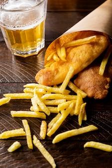 Peixe com batata frita em casquinha de papel com cerveja