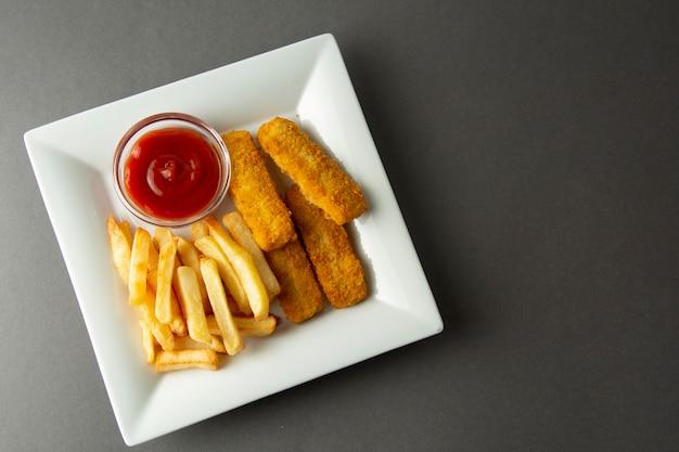 Peixe com batatas fritas com batatas fritas - alimento insalubre, backgrpound cinzento.