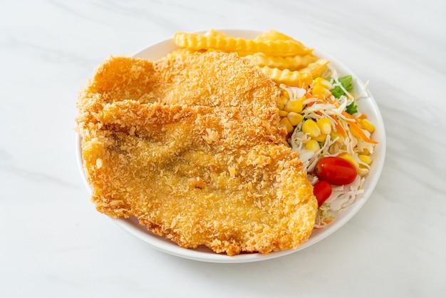Peixe com batatas fritas com mini salada no prato branco