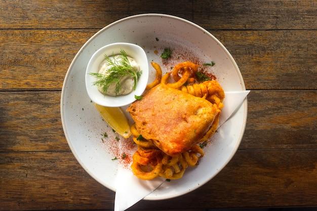 Peixe com batatas fritas com molho tártaro em um prato sobre uma mesa de madeira