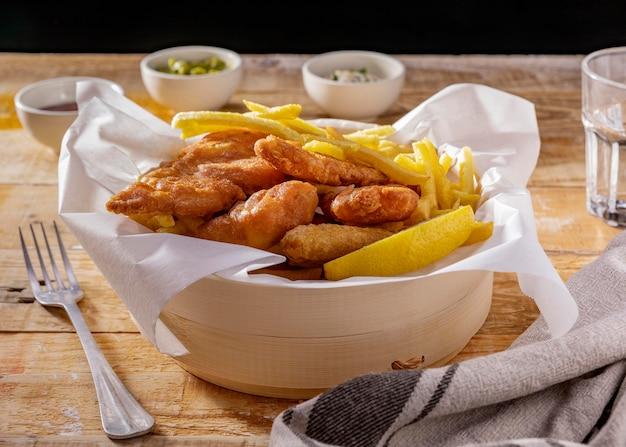 Peixe com batatas fritas em tigela com molhos