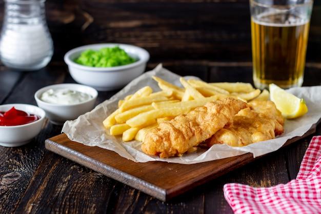 Peixe com batatas fritas em um de madeira. fast-food britânico. receitas. lanche de cerveja. cozinha inglesa.