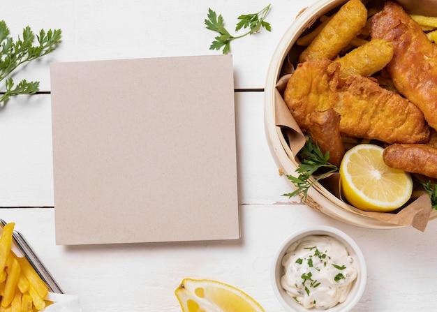 Peixe com batatas fritas em uma tigela com limão e cartão