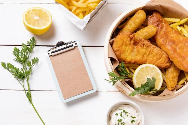 Peixe com batatas fritas em uma tigela com limão e prancheta