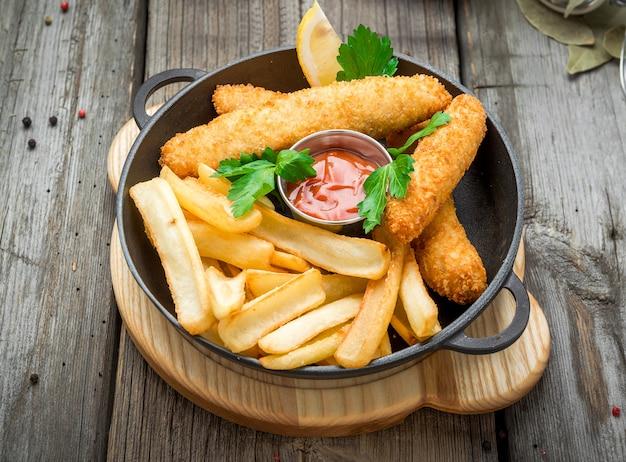Peixe com batatas fritas na mesa de madeira, comida saborosa.