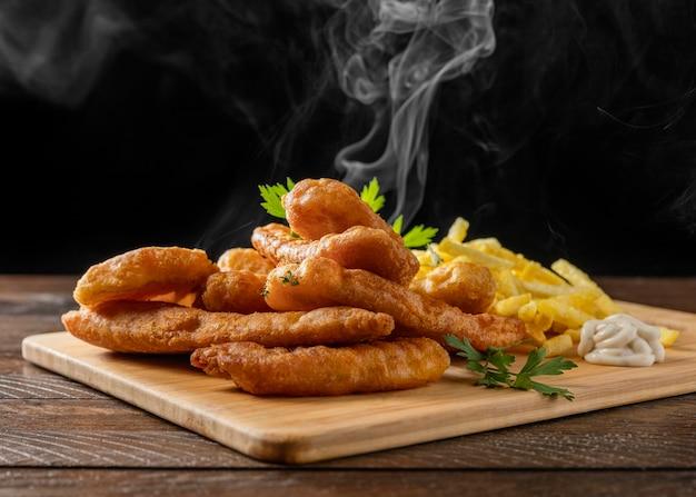Peixe com batatas fritas na tábua de cortar com vapor