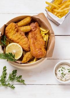 Peixe com batatas fritas na tigela com limão