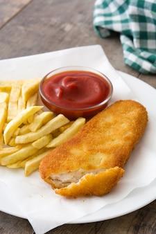 Peixe com batatas fritas tradicional britânico na mesa de madeira.