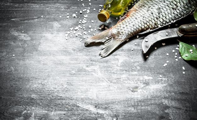 Peixe com uma faca de trinchar velha e azeite. sobre um fundo preto de madeira.