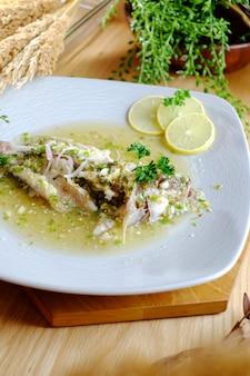 Peixe cozido com aipo e limão fatiado no prato