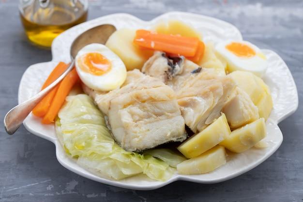 Peixe cozido com legumes e ovo cozido no prato branco