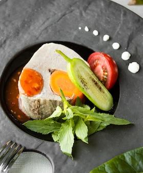 Peixe cozido com legumes em cima da mesa
