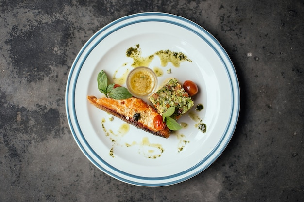 Peixe cozido com molho de tomate em um prato branco