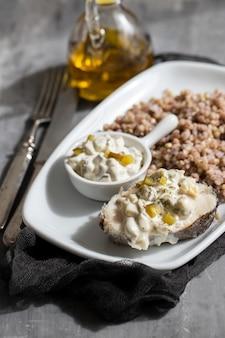Peixe cozido com trigo sarraceno e molho no prato branco sobre fundo de cerâmica