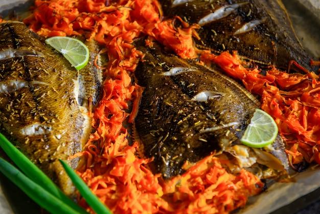 Peixe cozido na assadeira com legumes, close-up. solha em pergaminho com cenoura, limão e cebolinha.