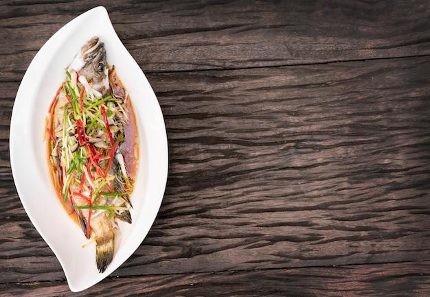 Peixe cozido no vapor com molho de soja na chapa branca na mesa de madeira.