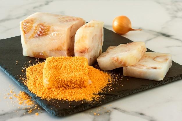 Peixe cru bloqueado em migalhas em uma placa de pedra preparada para fritar.
