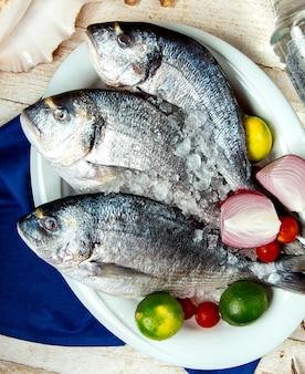 Peixe cru, colocado no prato com cebola limão tomate cereja e gelo
