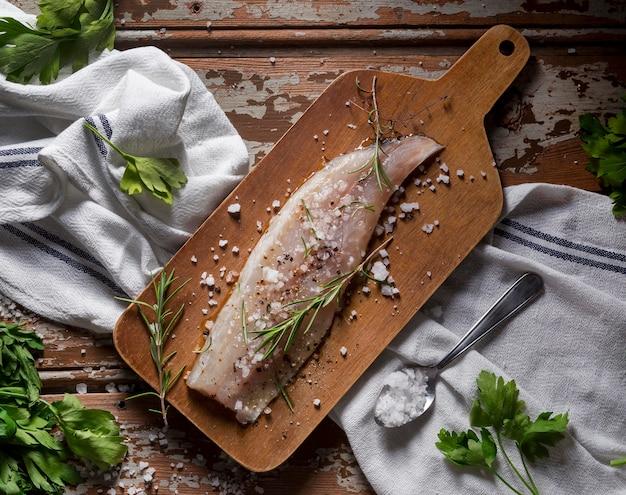 Peixe cru com composição de condimentos para cozinhar
