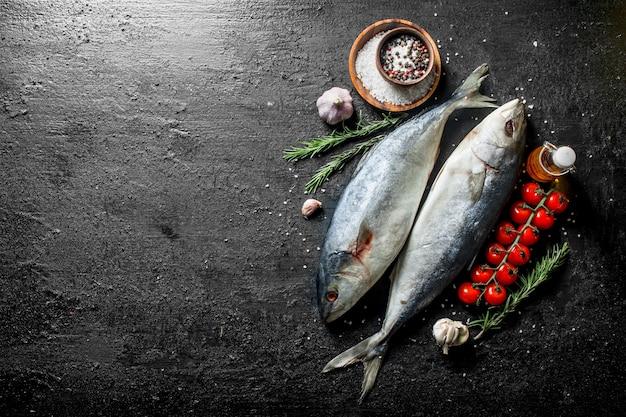 Peixe cru com especiarias, alecrim e dentes de alho na mesa rústica preta