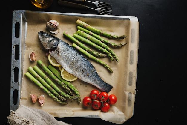 Peixe cru com especiarias e espargos vegetais na assadeira, pronto para ser cozido