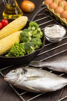 Peixe cru com legumes na grelha. ovo e farinha, garrafa com óleo.