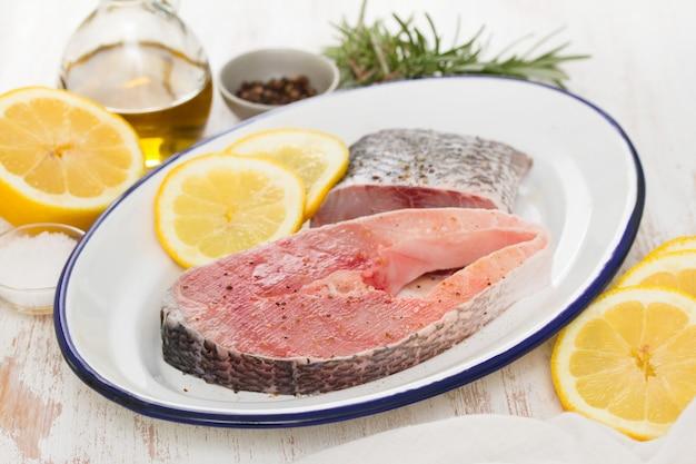 Peixe cru com limão no prato na superfície de madeira