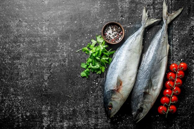 Peixe cru com salsa, tomate e especiarias na mesa rústica.