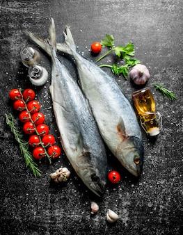 Peixe cru com tomate no galho, verduras e óleo na mesa rústica.